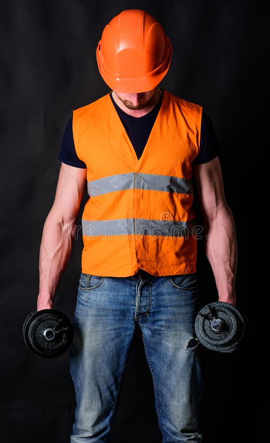 Worker, contractor, builder on busy face with muscular biceps. Strong builder concept. Builder in helmet working out royalty free stock photo