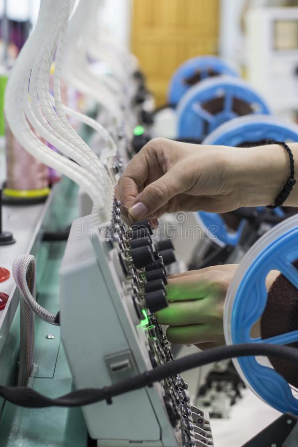 Worker corrects embroidery thread on the embroidery device.  stock photography