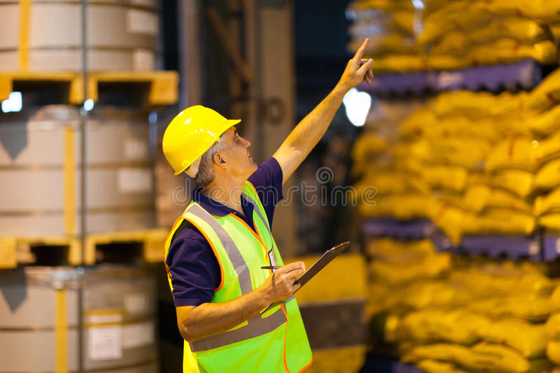 Worker counting pallets. Middle aged shipping company worker counting pallets in warehouse before dispatching royalty free stock photography