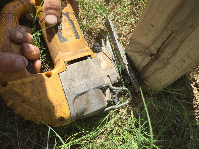 The worker cut post. The worker cut wooden fence with power saw royalty free stock images