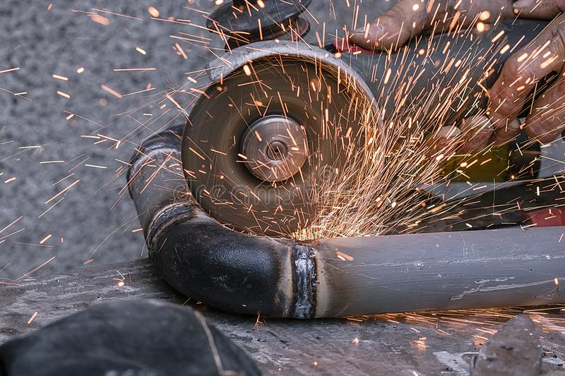 Worker cuts a metal pipe by means of the abrasive tool royalty free stock photo