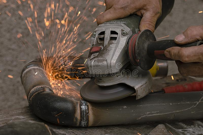 Worker cuts a metal pipe by means of the abrasive tool stock images
