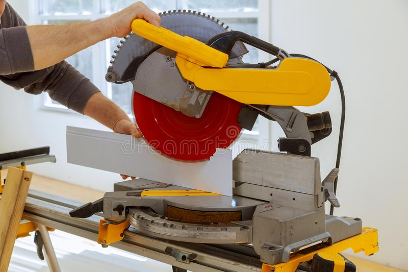 Worker cuts wood baseboard on the power miter saw. New home before installing stock image