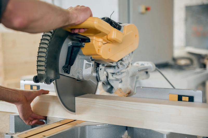 Worker cuts a wooden beam circular saw. Modern equipment stock image