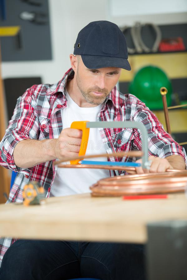 Worker cutting copper pipe royalty free stock image