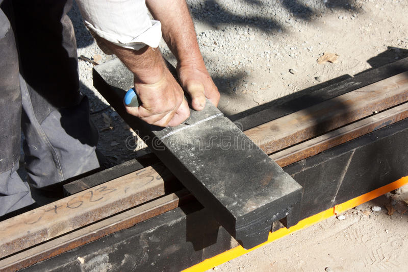 Worker cutting damping material for tram tracks. Man working on light rail construction site, cutting vibration damping material for tram rail tracks noise stock photo