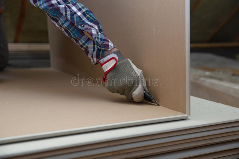 Worker cutting drywall plasterboard with construction knife. Attic renovation royalty free stock photography