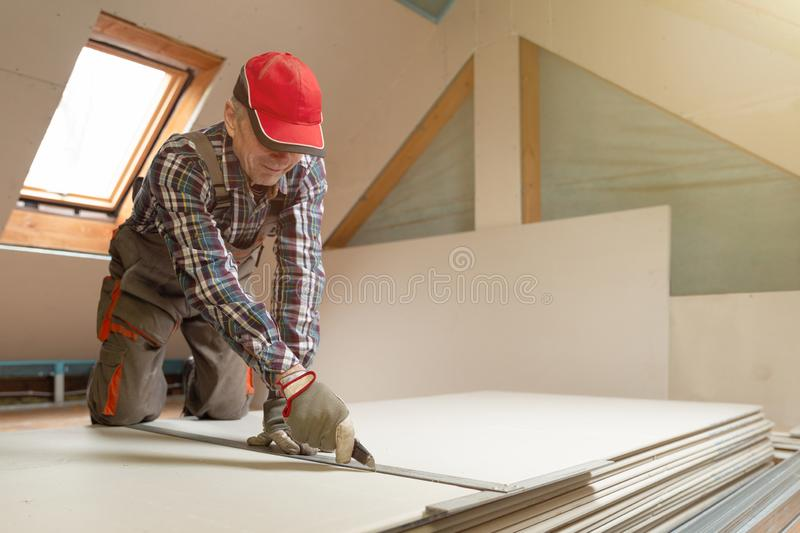 Worker cutting drywall plasterboard with construction knife. Attic renovation stock image