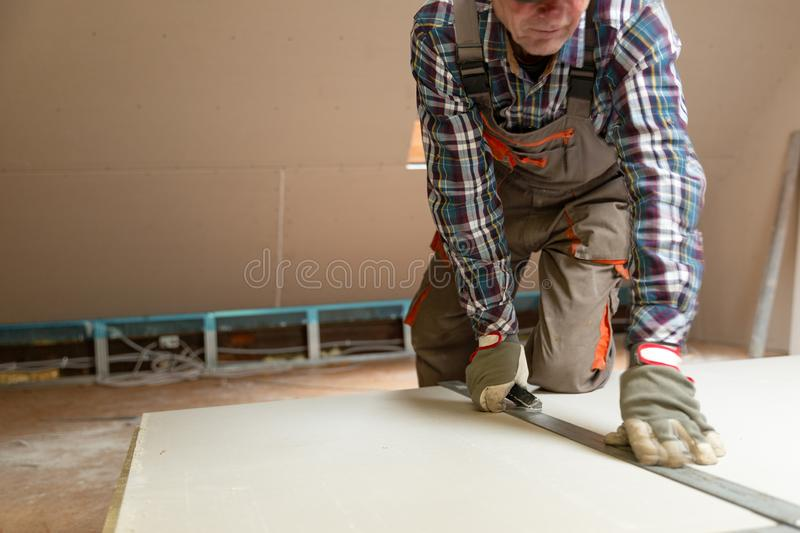 Worker cutting drywall plasterboard with construction knife. Attic renovation stock photo