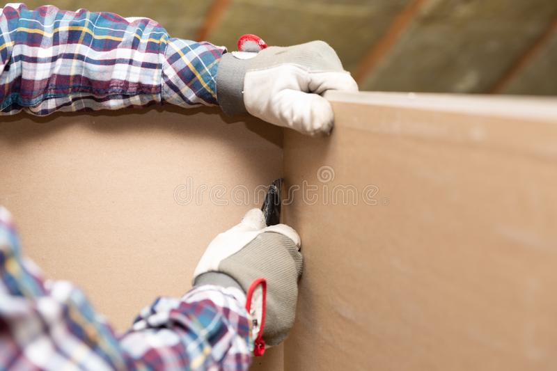 Worker cutting drywall plasterboard with construction knife. Attic renovation stock photography
