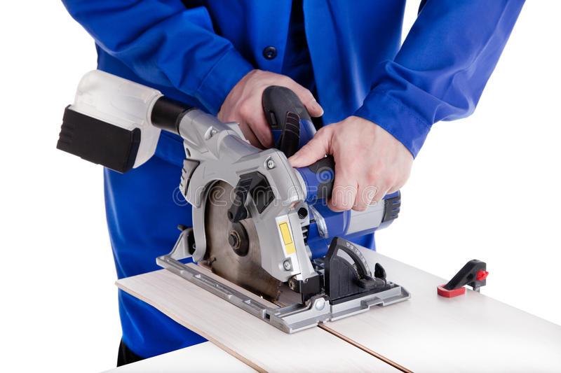 Worker cutting laminate with circular power saw. Worker in blue uniform cutting laminate with circular power saw, isolated on white stock images