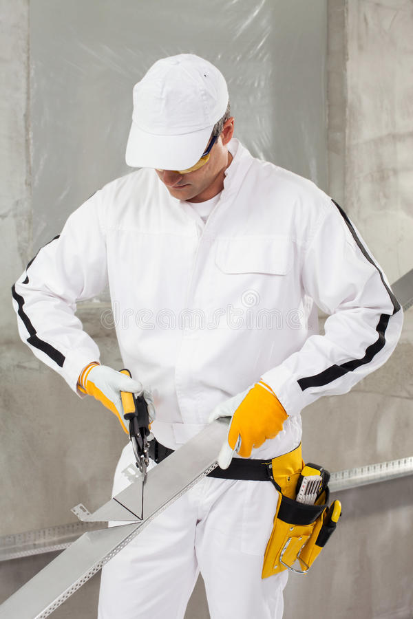 Worker cutting lath by stencil. Construction worker cutting lath by stencil stock photo