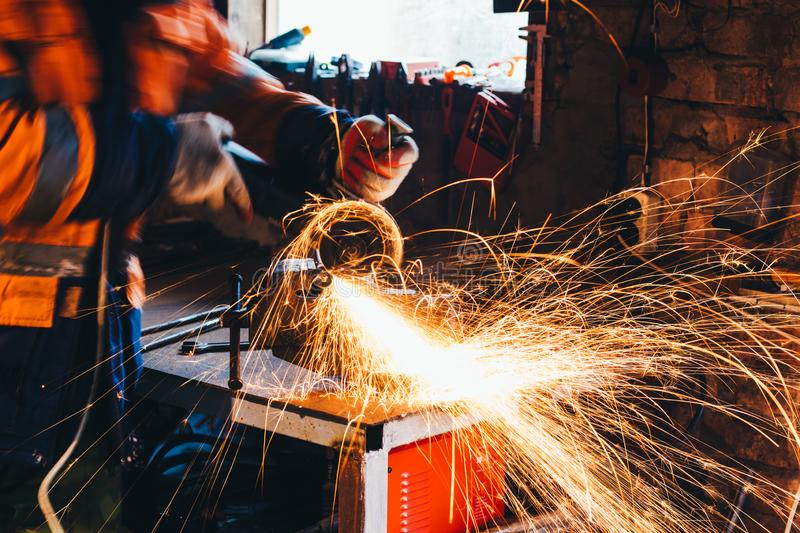 Worker cutting metal with grinder in his workshop. Sparks while grinding iron stock images