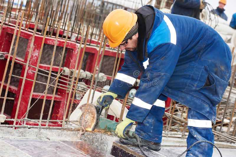 Worker cutting rebar by grinding machine royalty free stock images