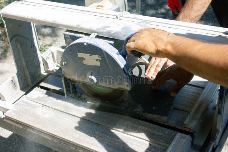 Worker cutting stone block by cutter machine stock image