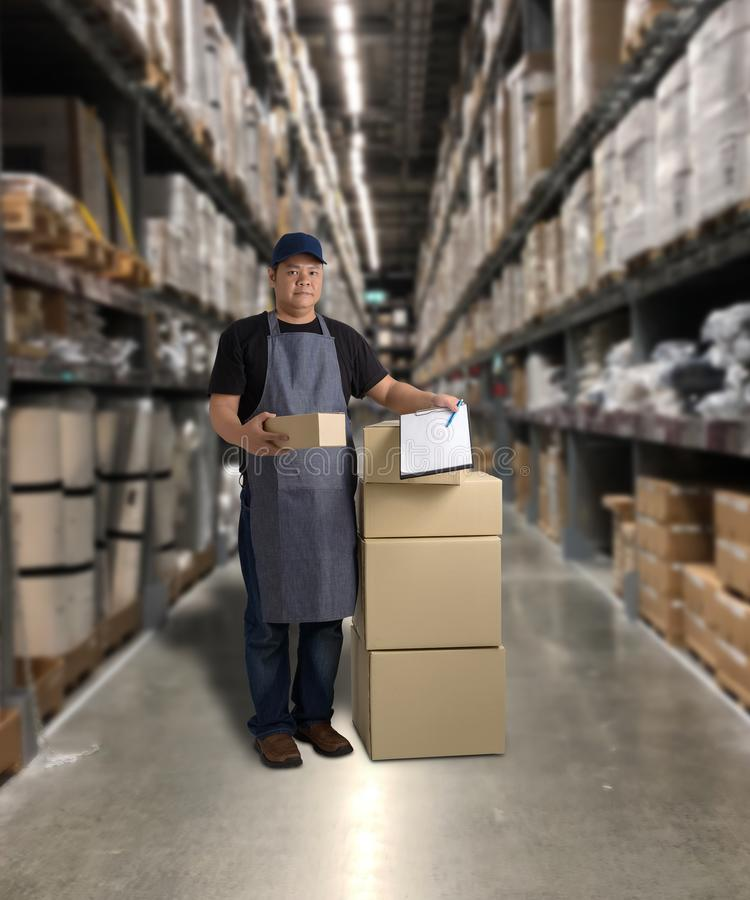 Worker Delivering products Sign the signature on the product receipt form with parcel boxes. Blurred the background of the warehouse royalty free stock photo