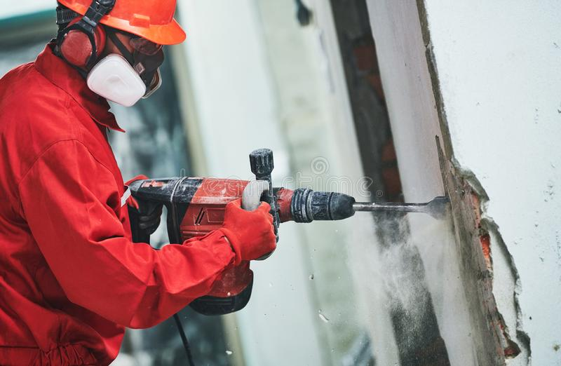 Worker with demolition hammer removing plaster or stucco from wall royalty free stock images