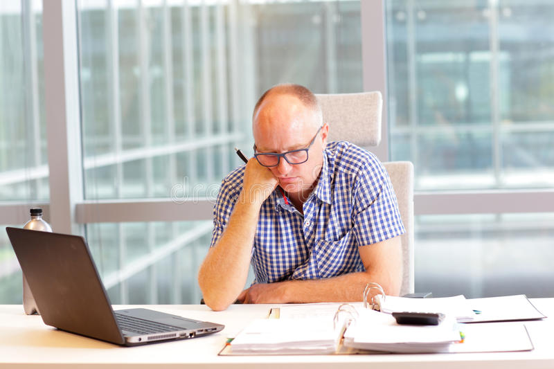 Middle aged man in hunched position at desk stock photography