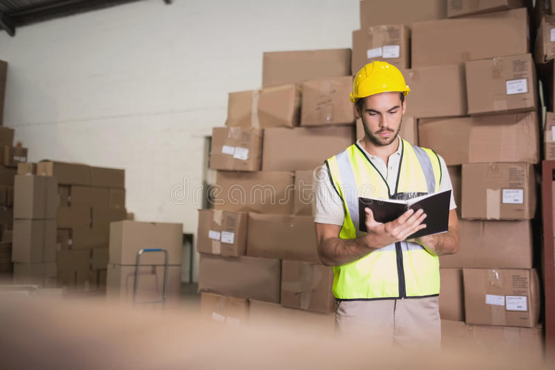 Worker with diary in warehouse stock images