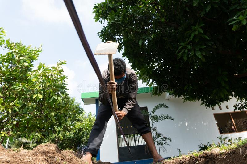 A worker is digging a hole by using hoe at the garden royalty free stock image