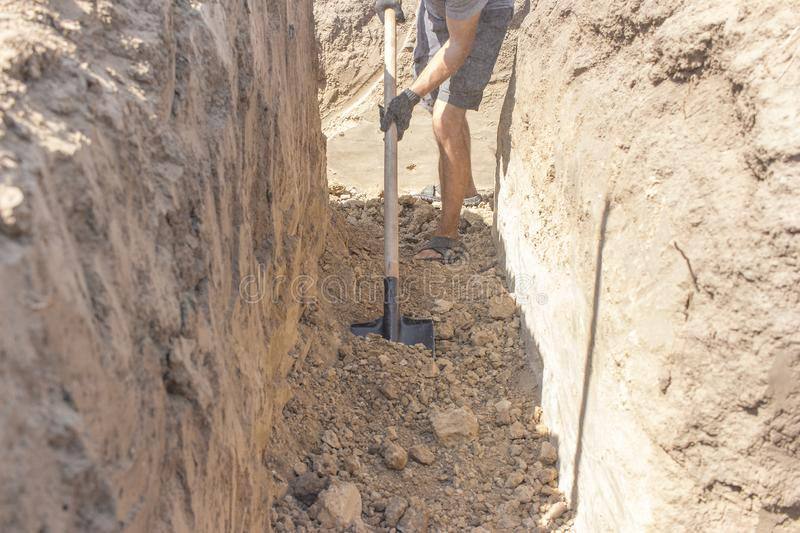 A worker digs a hole using a shovel / house building royalty free stock images