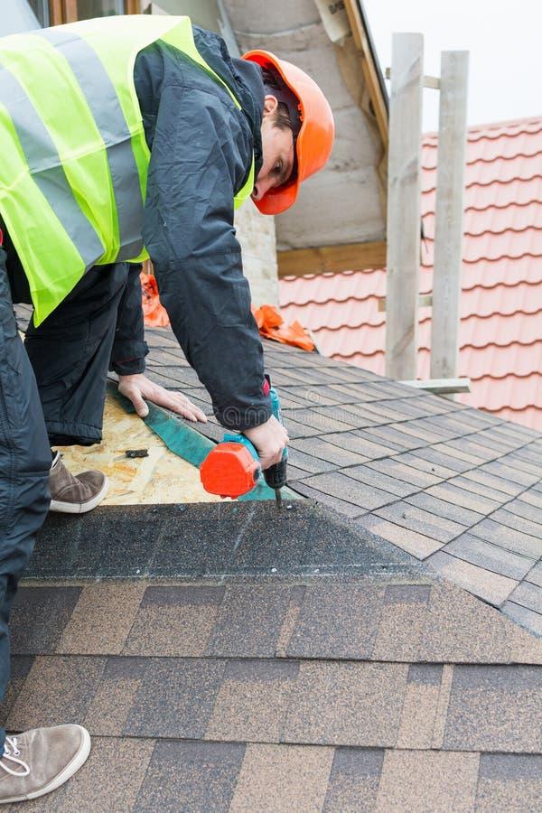 Worker dismantling roof shingles. Roofer builder worker dismantling roof shingles stock photography