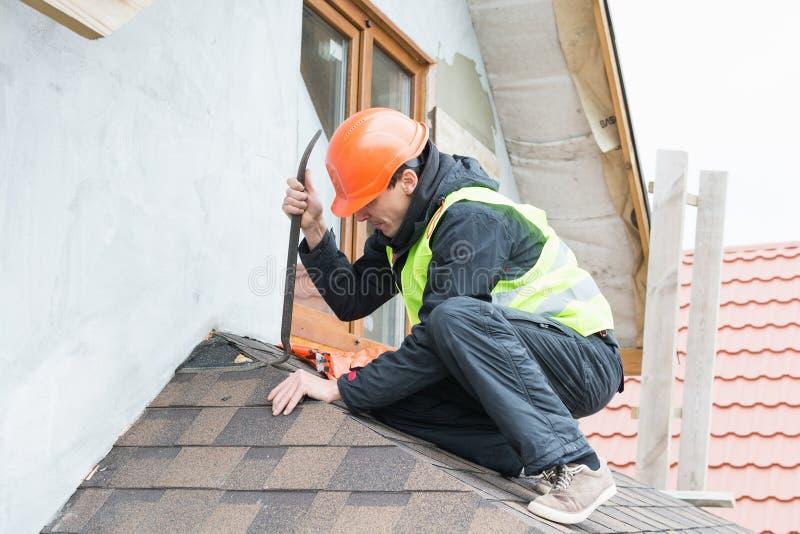 Worker dismantling roof shingles. Roofer builder worker dismantling roof shingles stock image
