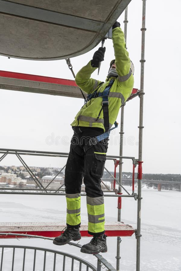 Worker dismantling temporary scaffolding wintertime. Workers dismantling temporary scaffolding after renovation of residential building in Stockholm, Sweden. The royalty free stock images