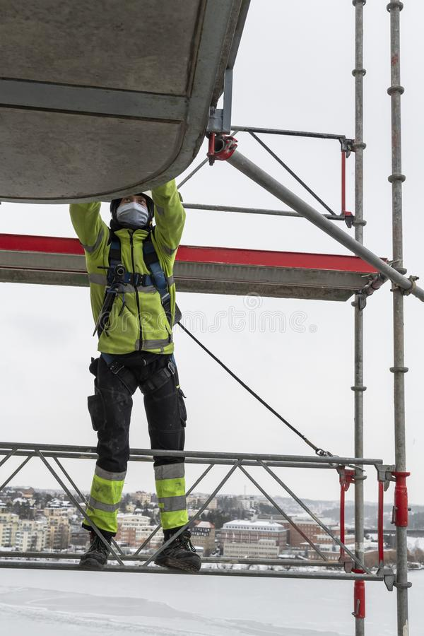 Worker dismantling temporary scaffolding wintertime. Workers dismantling temporary scaffolding after renovation of residential building in Stockholm, Sweden. The stock images