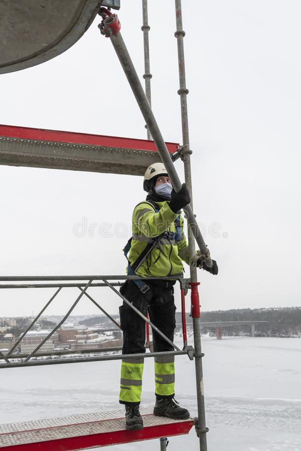 Worker dismantling temporary scaffolding wintertime. Workers dismantling temporary scaffolding after renovation of residential building in Stockholm, Sweden. The stock photo