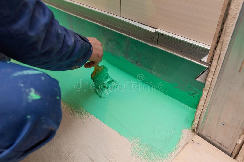Worker is doing waterproof finish the bathroom floor in apartment is inder construction, remodeling, renovation. Worker is painting by brush with green colored royalty free stock images