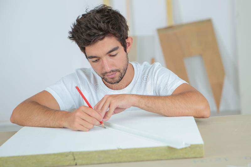 Worker drawing mark on laminate using ruler. Worker drawing a mark on laminate using ruler royalty free stock photos