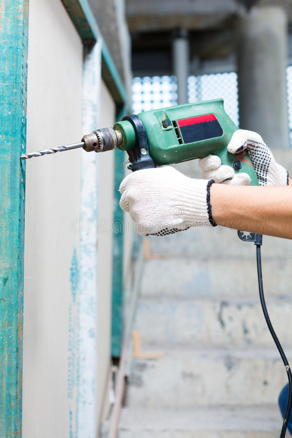 Worker drilling with machine in construction site wall. Asian Indonesian builder or craftsman drilling with a machine or drill, protection gloves and tools in a stock photography