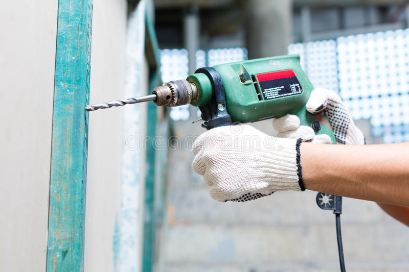 Worker drilling with machine in construction site wall. Asian Indonesian builder or craftsman drilling with a machine or drill, protection gloves and tools in a royalty free stock photography