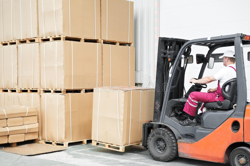 Worker driver at warehouse forklift. Young cheerful warehouse worker driver in uniform driving forklift stacker loader royalty free stock photos