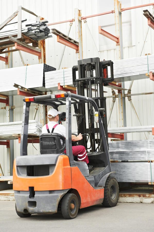 Worker driver at warehouse forklift. Young cheerful warehouse worker driver in uniform driving forklift stacker loader stock photos