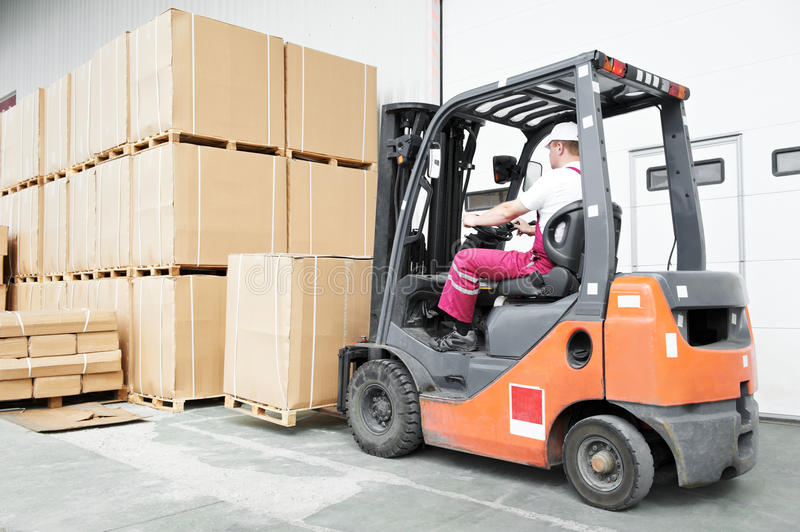 Worker driver at warehouse forklift. Warehouse worker driver in uniform stacking cardboxes by forklift stacker loader royalty free stock image
