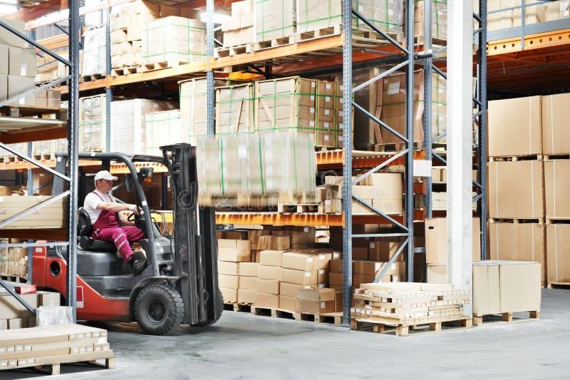 Worker driver at warehouse forklift loader works. Warehouse worker driver in uniform loading cardboxes by forklift stacker loader royalty free stock images