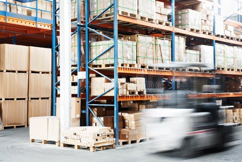 Worker driver at warehouse forklift loader works. Warehouse worker driver in uniform loading cardboxes by forklift stacker loader stock photography