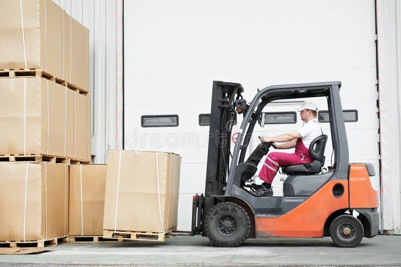 Worker driver at warehouse forklift loader works. Warehouse worker driver in uniform stacking cardboxes by forklift stacker loader royalty free stock images