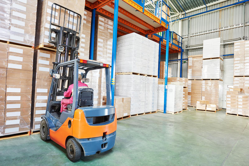 Worker driver at warehouse forklift loader works. Warehouse worker driver in uniform stacking cardboxes by forklift stacker loader royalty free stock photos
