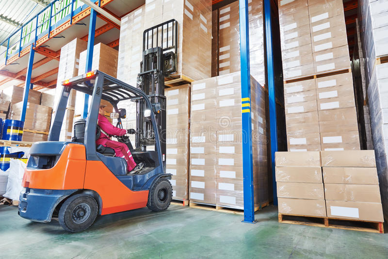 Worker driver at warehouse forklift loader works. Warehouse worker driver in uniform stacking cardboxes by forklift stacker loader stock images