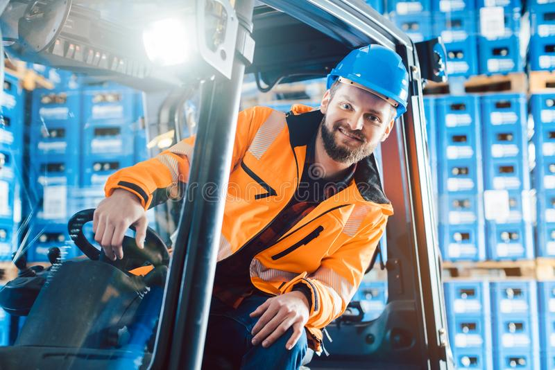 Worker driving a forklift in logistics delivery center. Looking into the camera royalty free stock photos