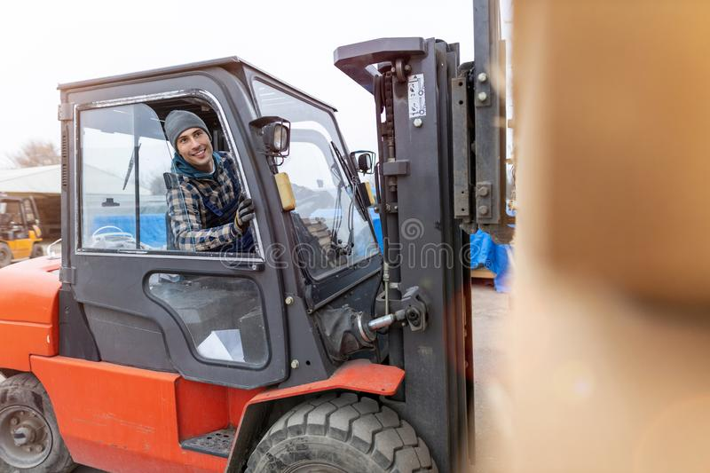 Worker driving forklift in lumber yard stock image