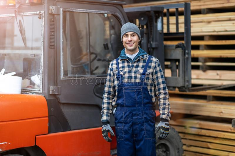 Worker driving forklift in lumber yard stock images