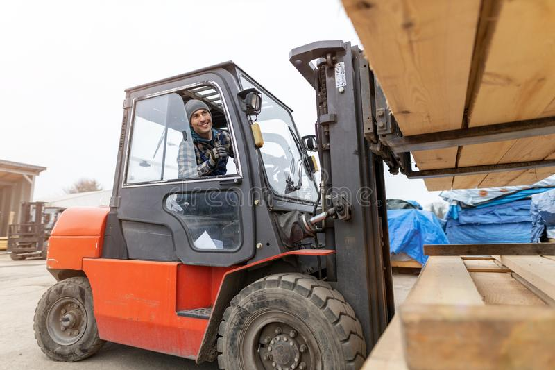 Worker driving forklift in lumber yard stock photos