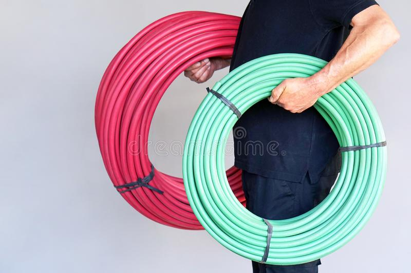 Worker with electrical protective tube. The electrician holds green and red a roll of an electric protective tube on a gray background. The concept of industrial stock image