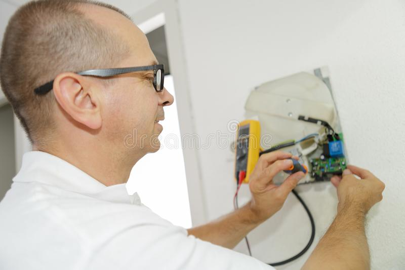 Worker electrician installs electrical outlet in apartment stock image