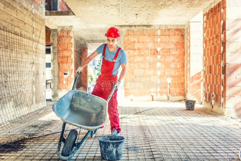 Worker with empty wheelbarrow on construction site stock photos