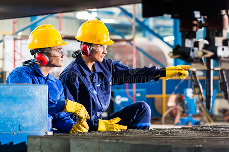 Worker in factory at industrial metal cutting machine stock photos